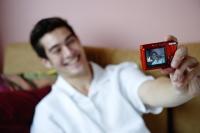 Man holding camera, taking photograph of himself - Yukmin