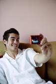 Man on sofa, holding camera, taking photograph of himself - Yukmin