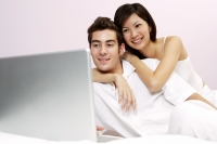 Couple on bed, looking at laptop, woman embracing man - Yukmin