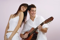 Man playing guitar, woman standing next to him smiling - Yukmin