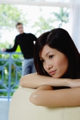 Woman leaning on back of sofa, looking away, man in the background - Yukmin