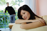 Woman leaning head on folded arms, looking away, man in the background - Yukmin