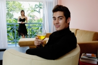 Man sitting in armchair in living room, holding a glass of wine, smiling, woman in the background - Yukmin