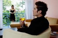 Man sitting in living room with a glass of wine, woman standing in the balcony - Yukmin