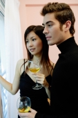 Couple holding wine glasses, looking away - Yukmin