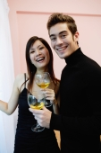 Couple holding wine glasses, standing side by side, smiling at camera - Yukmin