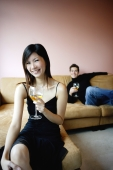Woman in black dress holding wine glass, smiling at camera, man in the background - Yukmin