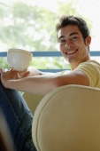 Man sitting on armchair, holding cup, smiling at camera - Yukmin