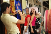Caucasian tourists trying on hats, man taking their picture with camera - Alex Microstock02