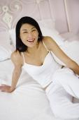 Woman sitting on bed, smiling at camera - Yukmin