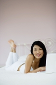 Woman in bedroom, using laptop, smiling at camera - Yukmin