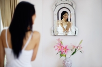 Woman applying make-up with brush, looking into mirror - Yukmin