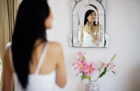 Woman looking into mirror, spraying perfume on neck - Yukmin