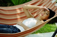 Woman lying on hammock, shielding eyes - Yukmin
