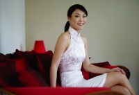 Woman dressed in Chinese cheongsam, sitting on red sofa, smiling at camera - Yukmin