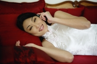 Woman dressed in Chinese cheongsam, lying on red sofa, using mobile phone - Yukmin