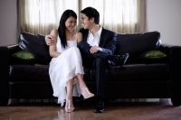 Well dressed couple sitting on sofa - Yukmin