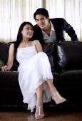 Woman sitting on sofa, man behind her, both looking at camera - Yukmin