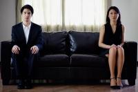 Man and woman sitting apart on sofa - Yukmin