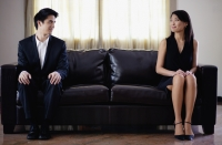 Man and woman sitting apart on sofa, turning to look at each other - Yukmin