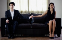 Man and woman sitting on sofa, holding hands - Yukmin