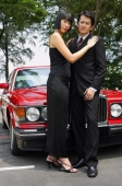 Well dressed couple standing in front of red car, woman with hands on man's shoulders - Alex Mares-Manton
