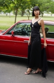 Woman in black dress standing next to red car - Alex Mares-Manton