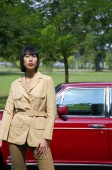 Woman in tan jacket standing next to red car - Alex Mares-Manton