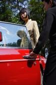 Man opening door of car for woman - Alex Mares-Manton