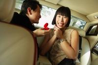 Couple sitting in backseat of car, man holding ring box, woman smiling at camera - Alex Mares-Manton