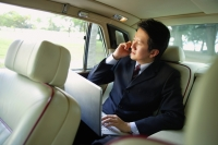 Businessman in car, using laptop and mobile phone - Alex Mares-Manton