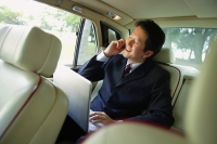 Businessman in backseat of car, using laptop and mobile phone - Alex Mares-Manton