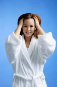 Young woman wearing white bathrobe, hands in hair - Alex Microstock02