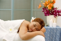 Young woman in spa, flower in hair, lying on massage table, eyes closed - Alex Microstock02