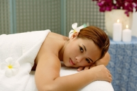 Young woman in spa, flower in hair, lying on massage table - Alex Microstock02