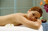 Young woman lying on massage table, looking at camera - Alex Microstock02