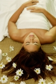 Young woman lying on back, flowers scattered around her - Alex Microstock02