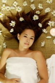 Young woman lying on back, flowers scattered around her, looking at camera - Wang Leng