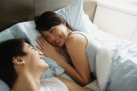 Couple lying in bed, smiling at each other - Alex Mares-Manton