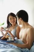Couple having breakfast in bed - Alex Mares-Manton