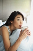 Woman sitting on bed, holding cup to lips, looking at camera - Alex Mares-Manton