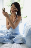 Woman sitting on bed, holding compact, applying make-up - Alex Mares-Manton