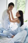 Couple in bedroom, woman adjusting man's tie, both smiling at camera - Alex Mares-Manton