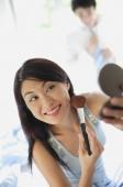 Woman applying make-up, looking at compact - Alex Mares-Manton