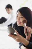 Woman looking at compact, applying make-up - Alex Mares-Manton