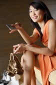 Woman holding shoes and credit card, smiling - Alex Mares-Manton