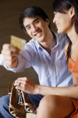 Woman holding shoes, man holding credit card towards camera - Alex Mares-Manton