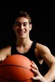 Man holding basketball towards camera, smiling - Alex Microstock02