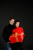 Couple standing side by side, woman holding big gift box - Alex Microstock02
