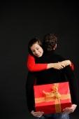 Man holding gift behind his box, woman embracing him - Alex Microstock02